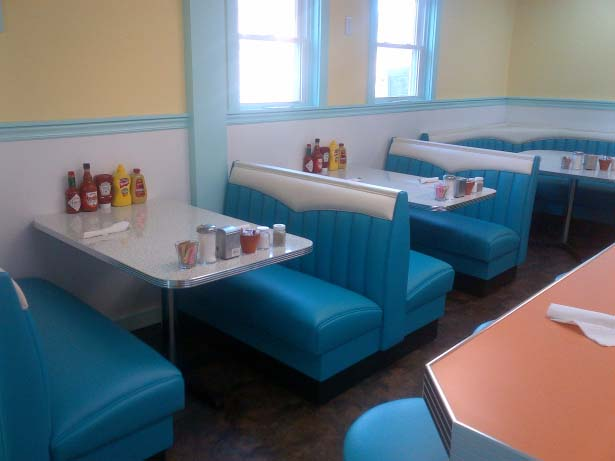 Small coffee shop with yellow walls, Formica tables in blue pleather booths.