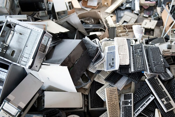 Small mound of e-waste comprised of old broken keyboards, PC cases, desktops, towers, etc.