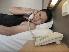Half asleep guy answering hard line phone next to bed.
