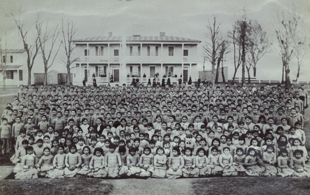 Old black and white photo of hundreds of Native American Boarding School Students posing for school photo.