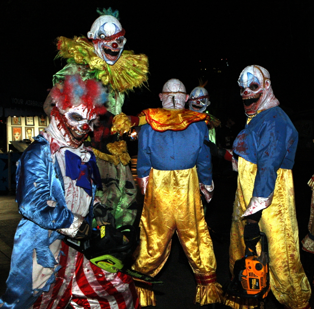 Five Bloody Evil Clowns outside holding chainsaws at night.