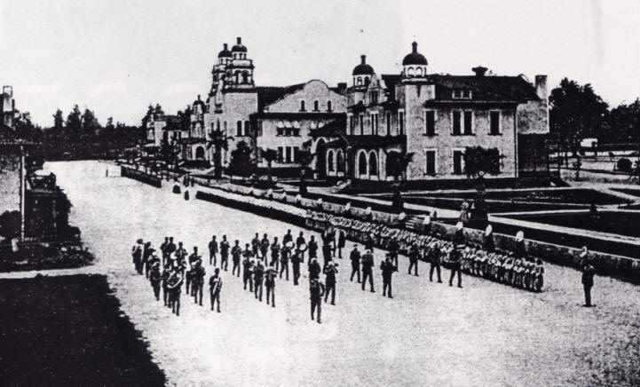 Old black and white photo of an early Native American Boarding School with a Band Marching in a Parade.