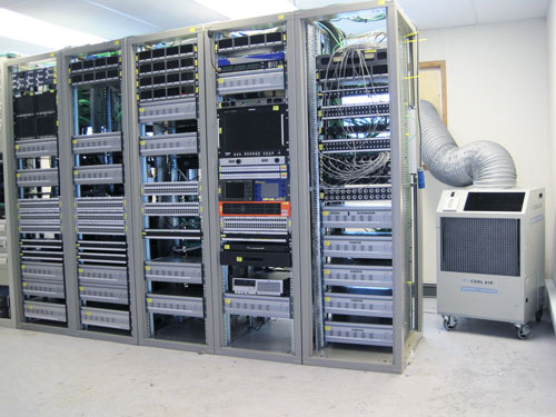 I.T. Server Rack with  portable rolling Air Conditioner next to it inside of a Network Server Room.