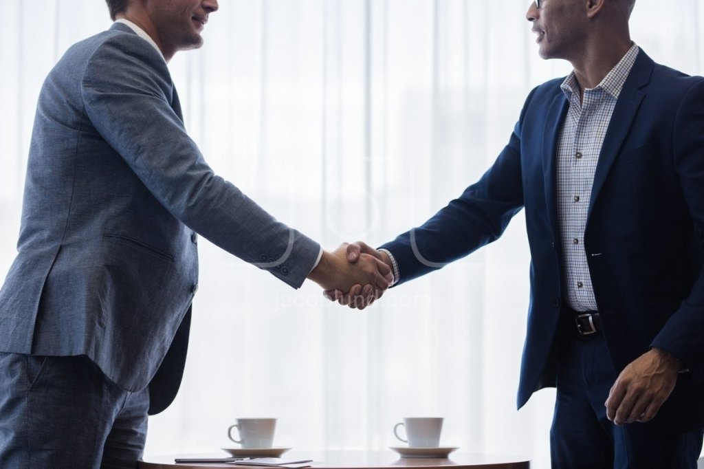 Two professionally dressed businessmen respectfully shaking hands over a coffee table.