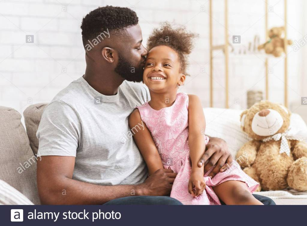 A Black Father lovingly kissing his young Black Daughter sitting on his knee.