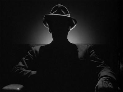 Shadowy Man wearing Fedora Hat sitting in Darkness